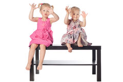 Girls scaring on white background. Two funny girls scaring sitting on the table Stock Image