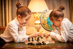 Girls in school uniform playing chess at cabinet Royalty Free Stock Photos