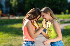 Girls are schoolgirls. Eat bananas for a break. Summer in nature. The concept of a healthy breakfast meal. Emotion is royalty free stock images