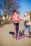 girls with scooter in spring park at warm day. Little adorable girls with scooter in spring park Stock Photo
