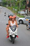 Girls on a Scooter. Tree girls on a motorbike in Phuket town January 24, 2018. The use of motorbikes as transport is common in Thailand.. Phuket island, Thailand Stock Image