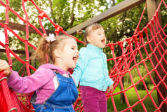 Girls screaming and standing on net of playground Royalty Free Stock Photos