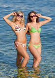 Girls at the sea. Two attractive girls in bikini smiling and looking through sunglasses at camera Royalty Free Stock Images