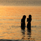 Girls in the sea at sunset. Two woman silhouettes in the water at the seaside in the sunset light royalty free stock images