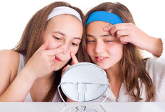 Girls searching for blemishes on theirs skin. Teeneger girls searching for blemishes on theirs skin Stock Photos