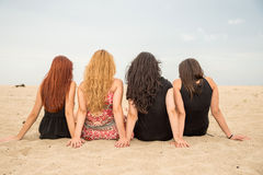 Girls seating on the beach. Summer holidays and vacation - girls seating on the beach stock photography