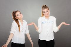 Girls seek a solution, making undecided gesture Stock Photo
