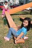 Girls on seesaw. Happy girls playing seesaw at the playground in the park on sunny day Royalty Free Stock Photos