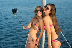 Girls with selfie stick smiling.