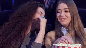 Girls share impressions at the movie theater. Two caucasian girls sharing impressions at the movie theater. Attractive curly woman telling something to her stock footage