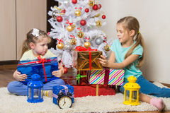 Girls share presented New Year gifts at the Christmas tree Royalty Free Stock Images