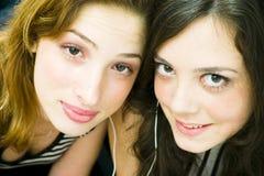 Girls sharing headphones Stock Images