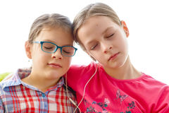 Girls sharing headphones to listen to music Royalty Free Stock Images