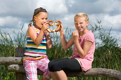 Girls sharing a pretzel Royalty Free Stock Images