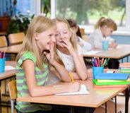 Girls sharing secrets in classroom.  Royalty Free Stock Photography