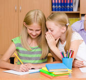 Girls sharing secrets in classroom Royalty Free Stock Photos