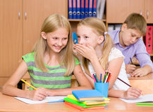 Girls sharing secrets in classroom Royalty Free Stock Photography