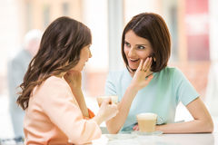 Girls sharing secrets. Two young beautiful girls sitting in urban cafe with coffee and sharing secrets Royalty Free Stock Photography
