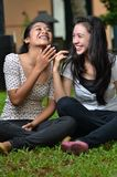 Girls sharing story or gossip 04. Two pretty southeast asian girls sharing exciting secret stories / gossiping (whispering to ears) with excitement at outdoor stock photo