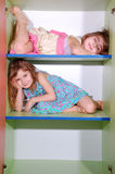 Girls on shelves. Two little friendly girls lying on shelves in a case with one shelf empty stock images