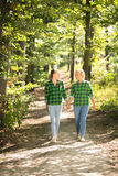 Girls in shirts and jeans walking in forest at sunny day Stock Photo
