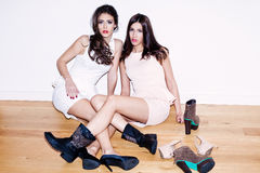 Girls and shoes. Couple of young women with lots of shoes on the floor Royalty Free Stock Photo
