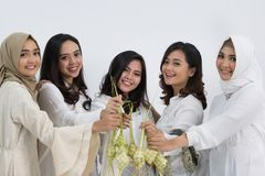 The girls shoot. The smiling girls are holding rice cake in front of the camera. muslim eid mubarak Royalty Free Stock Photo