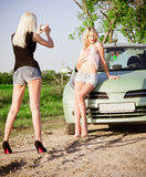 Girls shooting near a car Royalty Free Stock Images