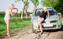 Girls shooting near a car Stock Photography