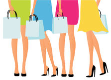 Girls shopping. Young girls in colorful dresses with shopping bags Stock Images