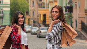 Girls with shopping bags on city street. Two smiling girls with shopping bags on city street. Young girls with shopping bags looking at camera and smiling stock video
