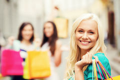 Girls with shopping bags in city. Shopping and tourism concept - beautiful girls with shopping bags in city royalty free stock photography