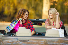 Girls with shopping bags in the convertible. Stock Photos