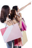 Girls with shopping bags pointing at copyspace Stock Photography