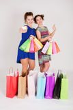 Girls with shopping bags. Showing empty business card Royalty Free Stock Image