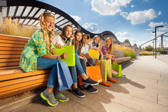 Girls with shopping bags sit close to each other Royalty Free Stock Image