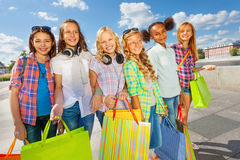 Girls with shopping bags walking close on road Stock Photos