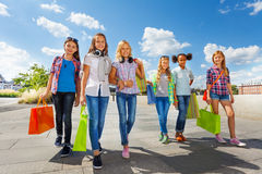 Girls with shopping bags walking together on  road. Girls with shopping bags walking together on stoned road and smile happily on urban background in summer Royalty Free Stock Photos