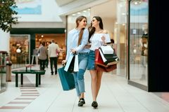 Girls Shopping. Female Friends In Mall. Girls Shopping. Beautiful Happy Female Friends With Colorful Bags Walking In Mall. High Resolution Royalty Free Stock Photos