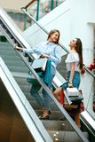 Girls Shopping. Female Friends In Mall. Girls Shopping. Beautiful Happy Female Friends With Colorful Bags Standing On Escalator Stairs In Mall. High Resolution Royalty Free Stock Photos