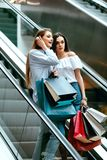 Girls Shopping. Female Friends In Mall. Girls Shopping. Beautiful Happy Female Friends With Colorful Bags Standing On Escalator Stairs In Mall. High Resolution Stock Photo