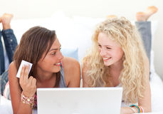 Girls shopping online in a bedroom Royalty Free Stock Photography