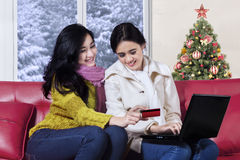 Girls shopping online with christmas tree background Royalty Free Stock Image