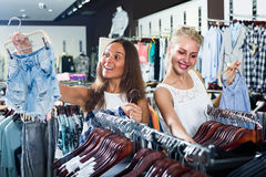 Girls shopping pair of denim shorts Stock Image