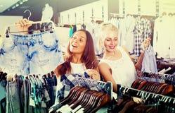 Girls shopping pair of denim shorts Stock Photography