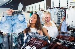 Girls shopping pair of denim shorts Stock Images