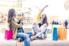 Girls shopping. Two pretty girls having fun while shopping outdoors - Best female friends spending time together Royalty Free Stock Image
