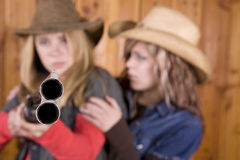 Girls with shotgun pointed one looking at other Royalty Free Stock Photos