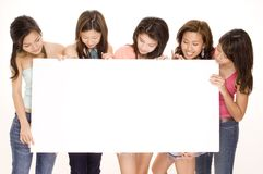 Girls and Sign #2. Five attractive young women hold and look at a big blank sign Royalty Free Stock Photo