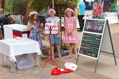 Girls with Christmas hats are singing Christmas carols, Australia. Girls are singing Christmas carols at the weekly sunday market in Alice Springs, Northern stock photography